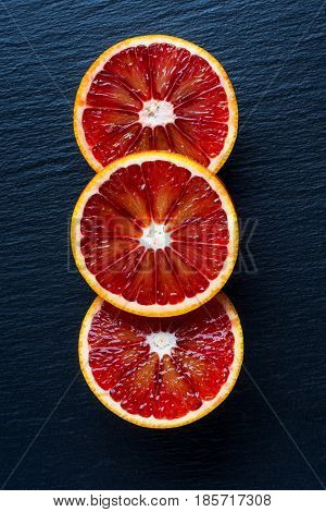Bloody Oranges on a black background. Top view