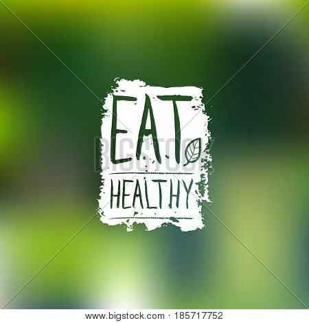 Eat healthy vector logo with handwritten lettering. Organic food label on blur background. Eco sign, Bio icon, badge for vegetarian restaurant, vegan cafe, product packaging.