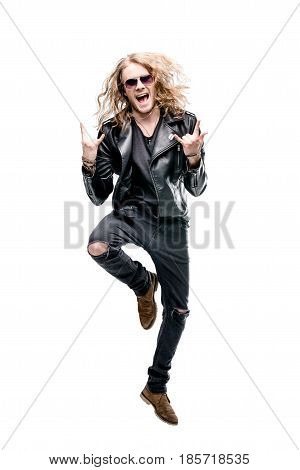 portrait of handsome rocker in black leather jacket showing rock signs isolated on white rock star concept