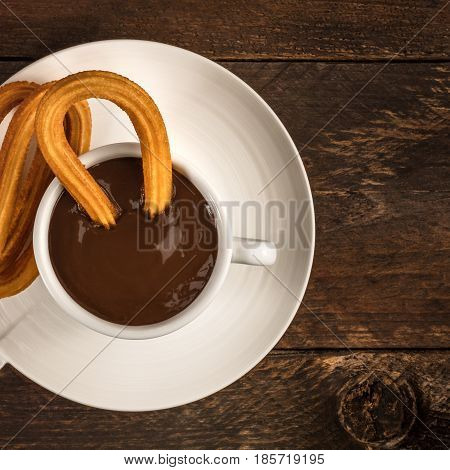 A square overhead photo of churros, traditional Spanish, especially Madrid, dessert, particularly for Sunday breakfast, with a cup of hot chocolate and a place for text