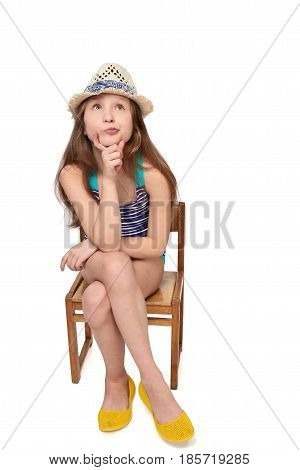 Full length child girl in swimsuit and summer hat sitting on wooden chair thinking contemplating looking up at blank copy space, studio portrait