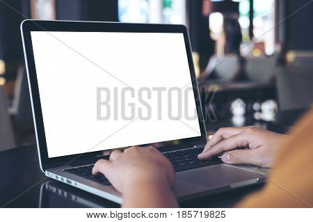 Mockup image of a woman using laptop with blank white screen on wooden table in modern cafe