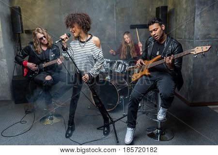 Young Rock Band Rehearsing In Musical Studio, Band On Stage Concept