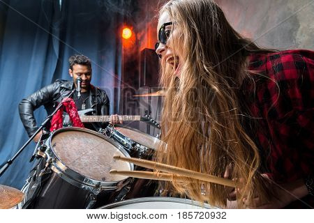 Side View Of Woman Playing Drums With Man Playing Guitar, Rock Band Concept