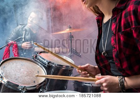 Side View Of Woman Playing Drums And Man Singing Into Microphone, Rock And Roll Band Concept