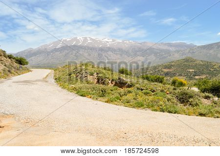 Winding road in the mountain of the center of Crete with the snowy ida mountain