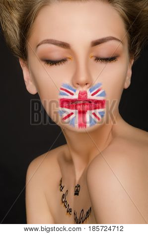 Young woman with english flag on her face black background