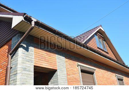 Rain gutter pipes against attic roofing. Guttering. Roof gutter.