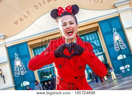 DISNEYLAND FRANCE - DECEMBER 8 2016:. happy elegant woman in red trench coat in the front of Disney Studio 1