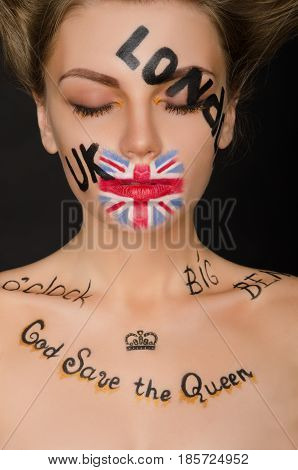 Young woman with english symbols on her face black background