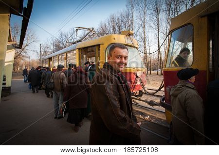 Spring. Tram station. Passengers get into the tram cars. The man is smiling. Photographed on the street. Proletarian. Kharkiv. Ukraine. 2007.03.20