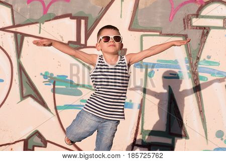 happy little boy with sunglasses and sailor vest put his hands to sides portraying the flight