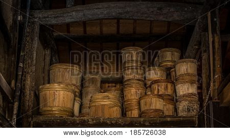 Rows of traditional wooden stake barrels with bamboo hoops wait on the street behind a soy souce brewing factory warehouse in Japan. Shodoshima Island
