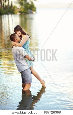 young couple in love at the rest on the nature. man and woman on the lake outdoors