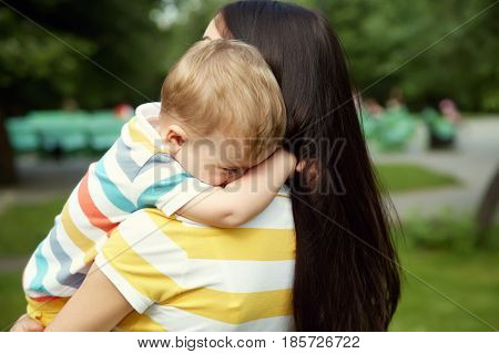 outdoor portrait of mother and son. child and mom walk in the summer park. sad crying baby