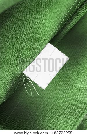 White blank clothes label on green silk closeup as a background