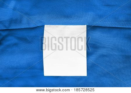 Blank white clothes label on blue cloth as a background