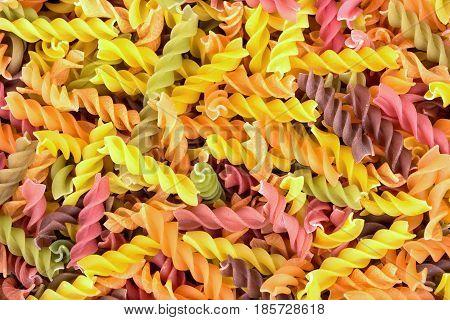 Background of colorful raw fusilli pasta closeup