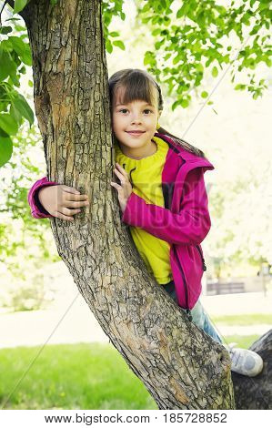 Funny playful little girl sitting on a tree in the park. children outdoors. vacation in the summer park