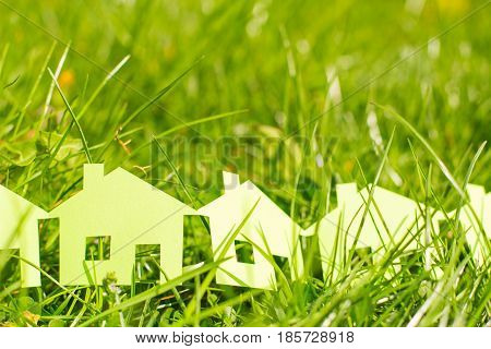 Construction of houses and cottages. Choosing a house when buying or renting. Green Cottage Town in grass.