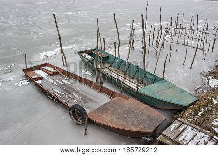 Two old wooden boat, one wrecked in a frozen river Tisa near Becej, Serbia. Winter time