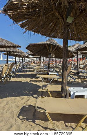 Beautiful Ionian sandy resort beach in Greece with sunbeds and straw sunshades, umbrellas. Vacation destination. Public beach