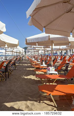 Beautiful Ionian sandy resort beach in Greece with sunbeds and canvas sunshades, umbrellas. Vacation destination. Public beach