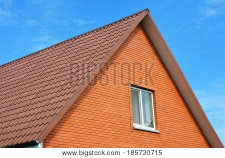 Red metal sheets house roof tiles. Metal Roof Shingles - Roofing Construction Attic Exterior Roofing Repair. Brick House.