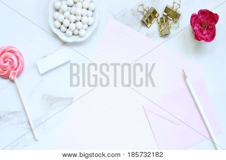 Chic and elegant desk top with pink, white and gold accessories. Copy space.