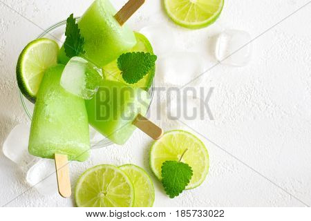 Healthy lime mint popsicles with fresh lime slices And ice cubes. Top view
