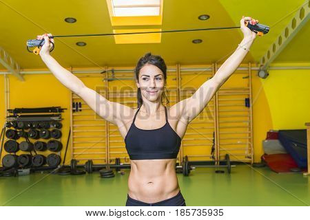 Strong young woman with gymnastics skipping rope