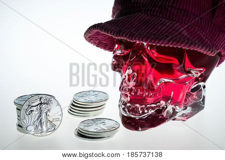 Investor red crystal skull glass brainpan with silver coins and white background