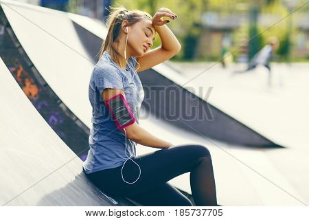 Pretty young woman having exercise outdoors on a sunny day