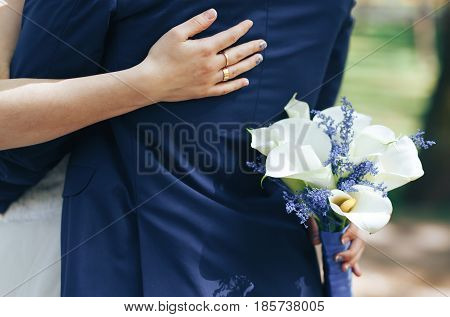 bride with wedding bouquet of white Calla lilies hugging the groom in a blue suit