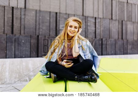 Urban Young Female Student Sitting Outside And Use The Phone