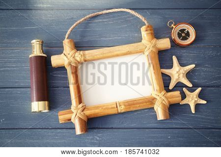 Travel concept. Bamboo frame with space for text, spyglass and compass on wooden background