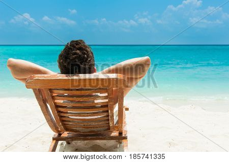 Man relaxing on beach ocean view Maldives island
