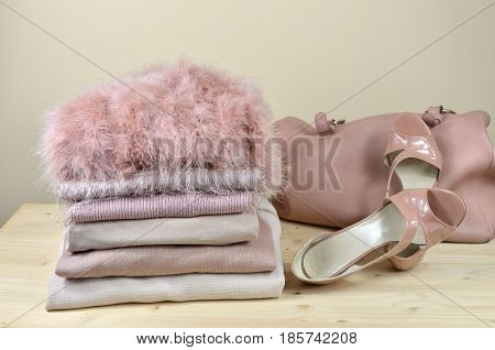 Pile of different pink garments with elegant pink sandals and a bag beside it - on wooden shelf