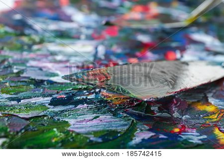 Colorful oil painting and palette knife, closeup