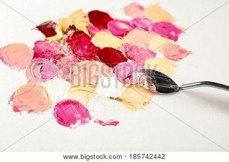 Palette knife with paint on canvas, closeup