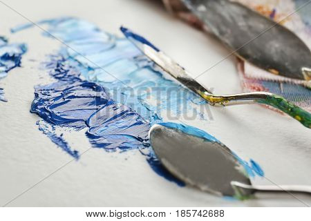 Palette knives with paint on canvas