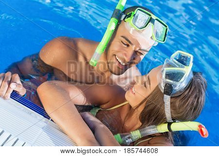 Beach travel couple having fun snorkeling. Happy young multiracial couple lying on summer beach sand with snorkel equipment looking to side at copy space after swimming with fins and mask on vacation