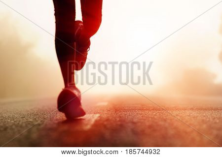 Runner athlete feet running on road. woman fitness silhouette sunrise jog workout wellness concept.