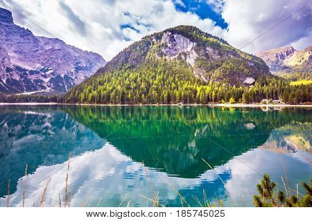 Magnificent lake Lago di Braies. South Tyrol, Italy. Emerald expanse of water reflects the surrounding forest and mountains. The concept of walking and eco-tourism