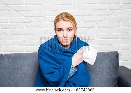 Young Woman Feeling Sick Or Sad Wrapped In Cozy Blue Blanket And Sitting On Sofa At Home