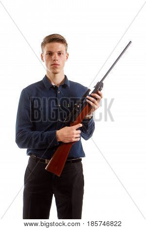 A young man wearing a shirt holding a brown rifle