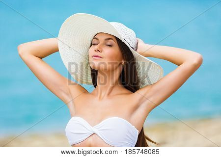 Relaxing beach woman enjoying the summer sun happy standing in a wide sun hat at the beach with face raised to the sunlight. Head and shoulder portrait. Multicultural Asian Caucasian in enjoyment