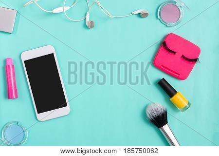 Female bag essentials, everyday make-up. Flat lay of cosmetics, mobile phone and headphones on bright blue background, objects