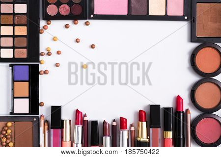 Makeup cosmetics, lipsticks and essentials frame on white background. Top view, flat lay with copy space. Beauty tools palettes collection, eyeshadow, blush, foundation and more