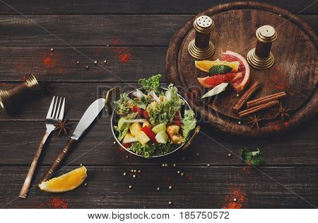 Indian restaurant, vegan and vegetarian dish, fresh vegetable salad in copper bowl. Lettuce and fruits mix with herbs, healthy meal, top view on wood background. Eastern local cuisine food.